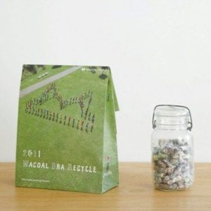 """A green + grass-print paper bag with """"Wacoal Bra Recycle"""" printed on it sits on a wooden surface. A clear jar of what looks like recovered fibre sits to the right of the bag."""
